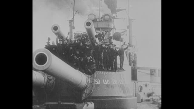 the german fleet surrenders to the british navy in wwi in operation zz / pan down from mast of german ship with flags flying to big guns on deck /... - military ship stock videos and b-roll footage