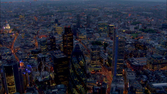 the gherkin glows near heron tower and tower 42 in london, england at night. - city of london stock videos & royalty-free footage