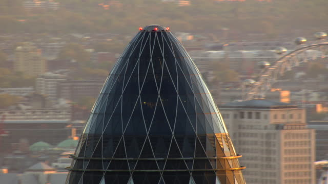 the gherkin towers near the london eye. - swiss re stock videos & royalty-free footage