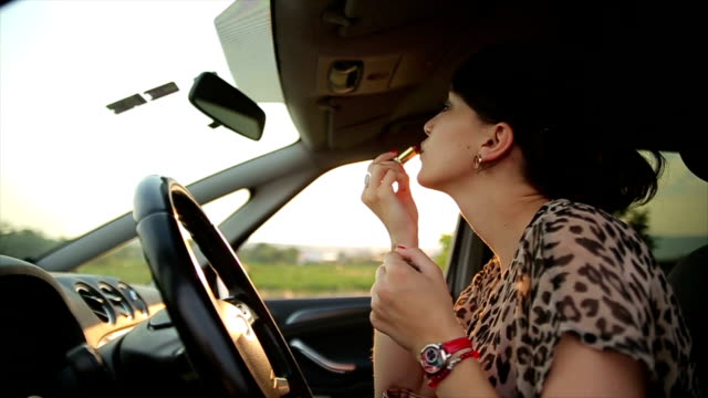 The girl fixes her make-up in the car