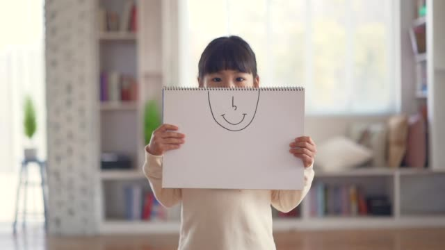 the girl holds a drawing paper with smile expression and has a happy look - offenes lächeln stock-videos und b-roll-filmmaterial