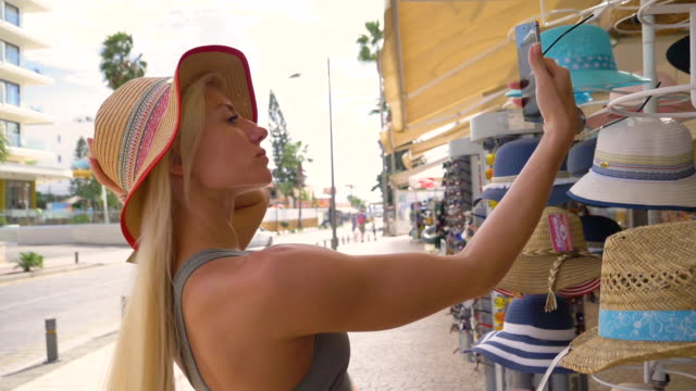 the girl in the hat tries on glasses - visual merchandising stock videos and b-roll footage