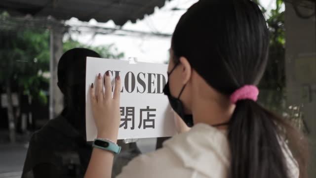 vídeos de stock, filmes e b-roll de a garota está fechando o letreiro da loja, loja fechando devido ao surto de pandemia do vírus covid-19 - placa
