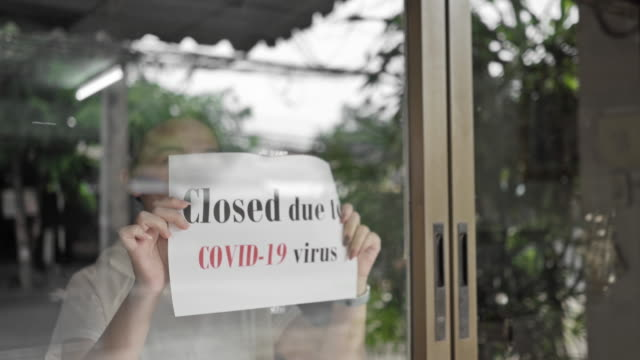 the girl is closing the store sign, store closing due to the covid-19 virus pandemic outbreak - closed stock videos & royalty-free footage