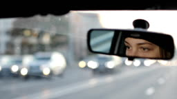 The girl is driving a car. Reflection of female eyes in the car rear view mirror.