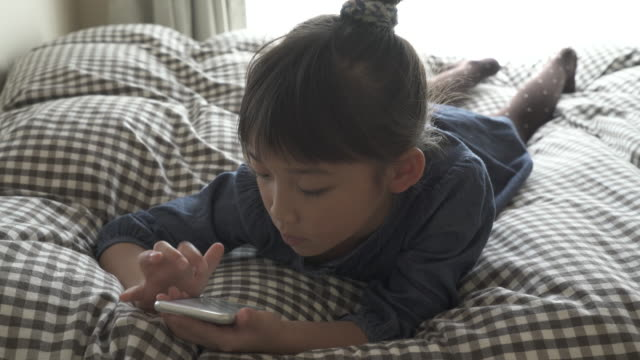 the girl is using a smart phone on the bed - アクセスしやすい点の映像素材/bロール
