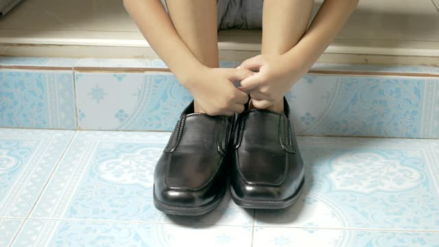 the girl is wearing his father's shoes. - footwear stock videos & royalty-free footage