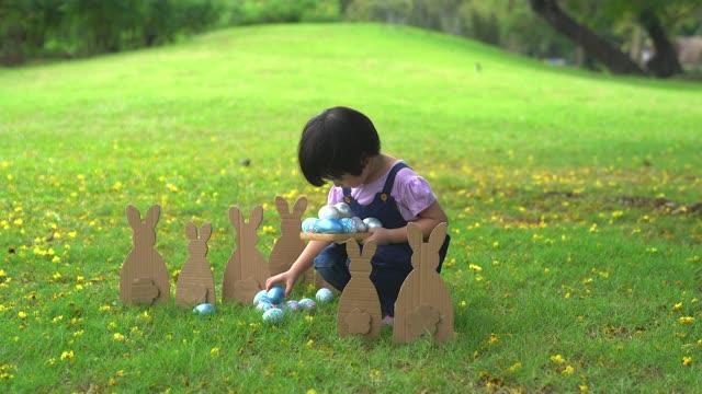 das mädchen hält einen korb mit ostereiern im park. - sammlung stock-videos und b-roll-filmmaterial