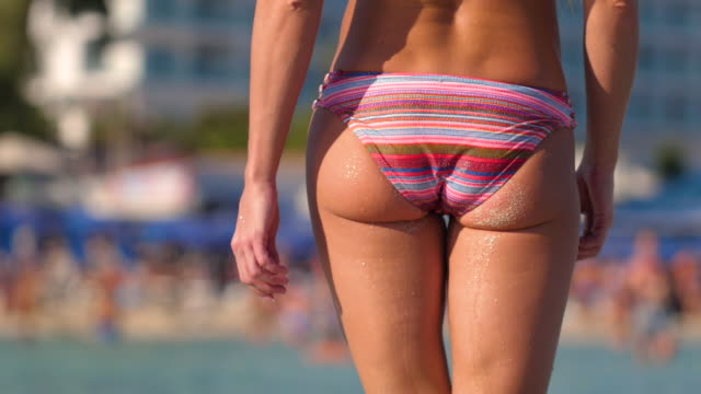 the girl on the beach against the backdrop of people - buttocks stock videos & royalty-free footage