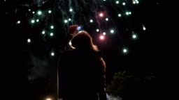The girl takes pictures of fireworks on a mobile phone. Silhouette on the background of the sky illuminated by lights