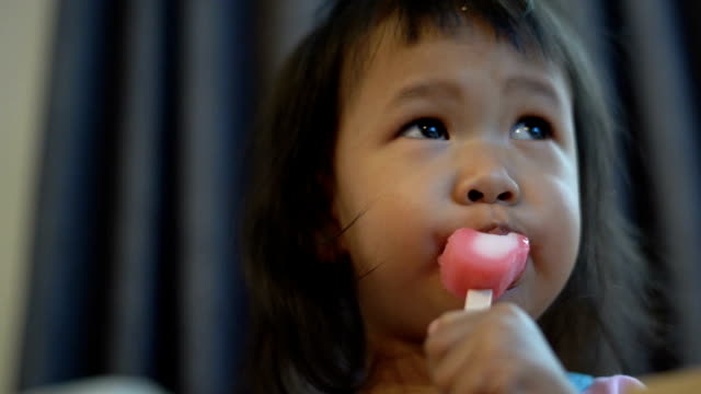 vídeos de stock e filmes b-roll de the girl wearing pink t-shirt eating pink ice cream. - língua humana