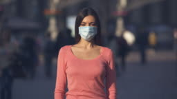 The girl with medical face mask stands in a crowded street