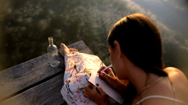 the girl writes a message on the dock , message in a bottle , beautiful autumn day - zen like stock videos & royalty-free footage