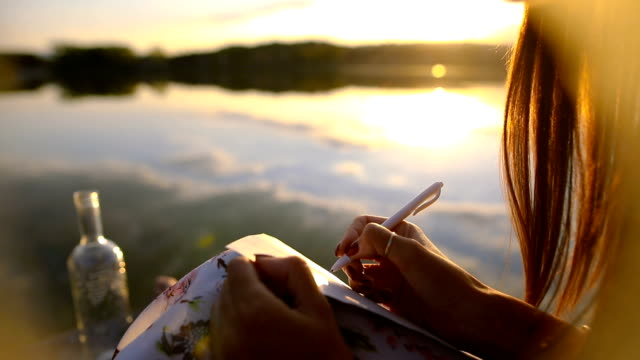 the girl writes a message on the dock , message in a bottle , beautiful autumn day - message stock videos & royalty-free footage
