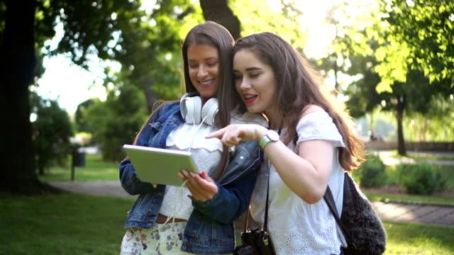 die mädchen in den park sehen sie die fotos, die sie gerade gemacht. - bild ambiente stock-videos und b-roll-filmmaterial