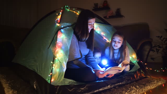 the girls read and study a book in a cute camping tent in the living room at home - electric lamp stock videos & royalty-free footage