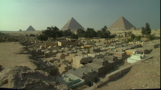 the giza pyramids dominate an egyptian skyline. - famous place stock videos & royalty-free footage