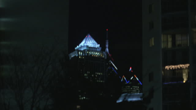 stockvideo's en b-roll-footage met the glass dome of the mellon bank building glows at night. - bare tree