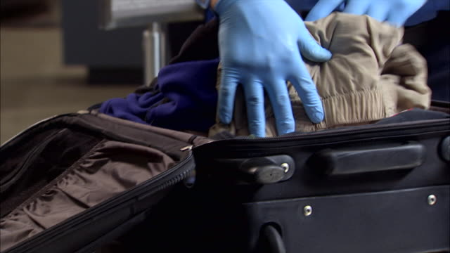 the gloved hands of an airport security agent search through clothing in a carry-on suitcase. - terrorism stock videos & royalty-free footage