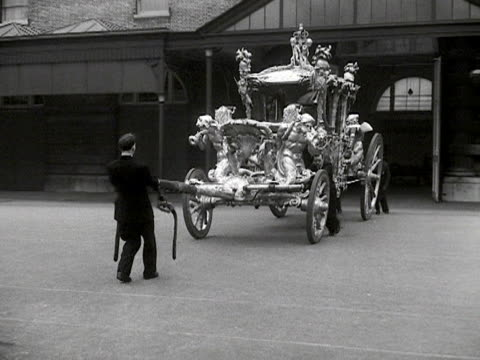 vídeos de stock e filmes b-roll de the gold state coach is pulled into the yard of the royal mews in preparation for the coronation of elizabeth the second. 1953. - carroça puxada por cavalo
