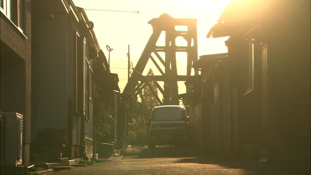 The golden hour sky contrasts with derelict buildings at Mitsubishi Kagayama Coal Mine.