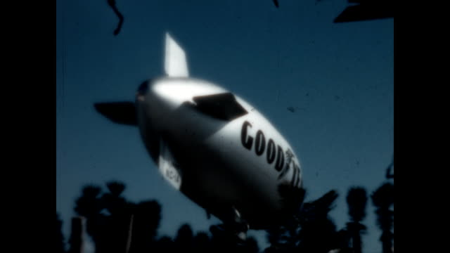 the goodyear blimp descends near the north bay of miami a seven seas cruise sightseeing boat passing along millionaires row in sunset lake - baia di biscayne video stock e b–roll