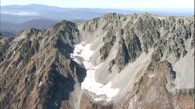 the gozenzawa perennial snow patch covers rugged slopes on the tateyama mountain range in japan. - perennial stock videos & royalty-free footage