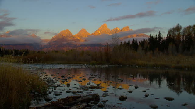 stockvideo's en b-roll-footage met the grand teton mountains glow with orange light above the snake river and schwabacher's landing. - snake river