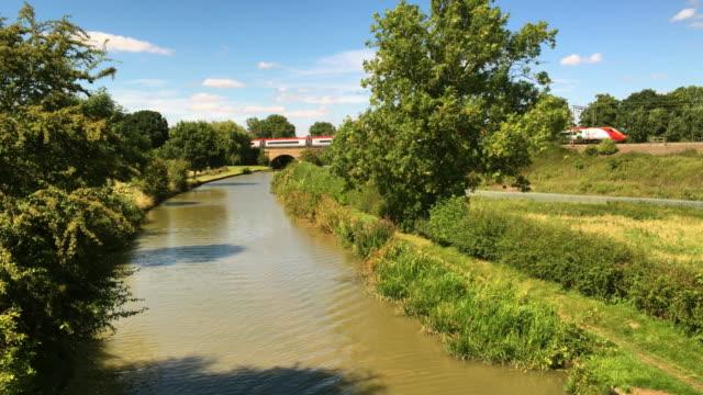 vidéos et rushes de the grand union canal with a virgin railway train in the background. - canal eau vive