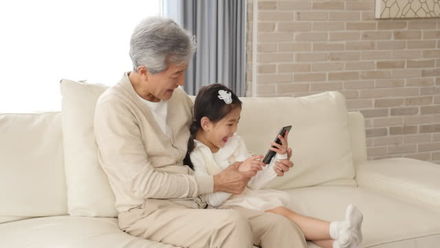 vídeos y material grabado en eventos de stock de the grandfather and granddaughter use a smartphone sitting on the couch - coreano oriental