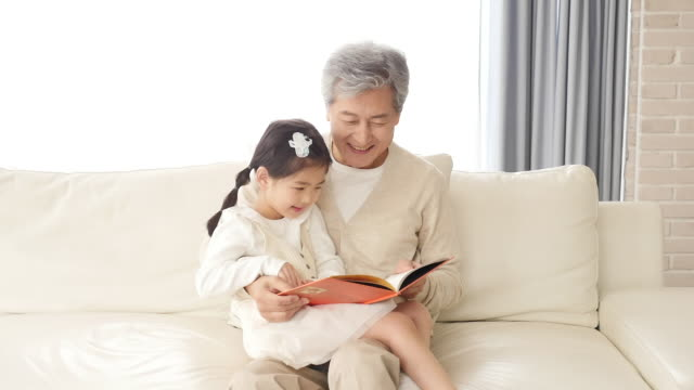 the grandfather reads a book with the granddaughter sitting on the couch - アクティブシニア点の映像素材/bロール