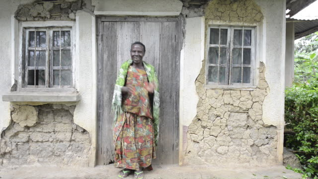 brac project, the grandmother of hilary mbajjo  (photographed) who is a brac mastercard scholarship recipient to attend private school. matilda nabbanja (72) wit her other grandsons, mutta joseph (21-blue), mbajjo francis (19) in their very rural home. - ブラック島点の映像素材/bロール