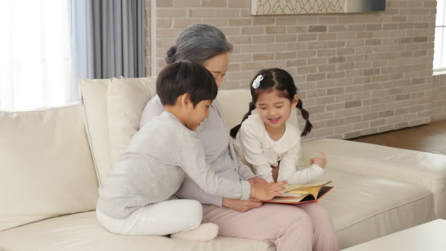 the grandmother reads a book with the grandchild sitting on the couch - 本点の映像素材/bロール