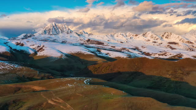 the grassland stretches to the foot of the snow mountain, and the sunset makes the snow mountain golden - distant stock videos & royalty-free footage