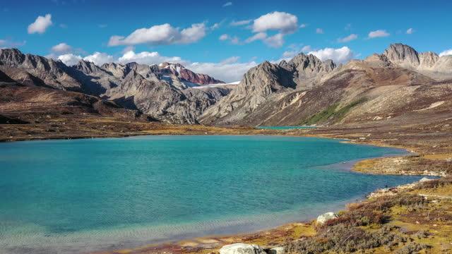 vídeos de stock, filmes e b-roll de o pasto se estende até a montanha de neve, eo lago está embutido nele - pureza