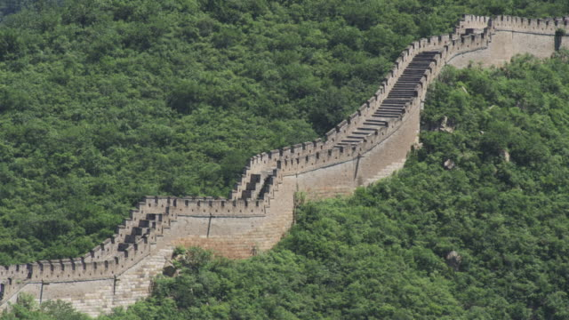 The Great Wall of China stretching out through lush mountains.