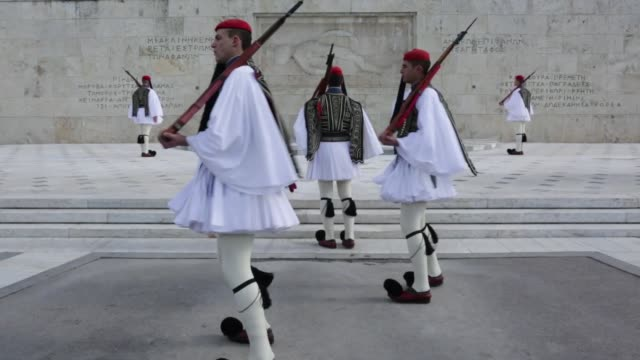 the greek national flag flies on top of the greek parliament in athens greece on tuesday december 6 evzone guards march in front of parliament gvs of... - religiöse stätte stock-videos und b-roll-filmmaterial