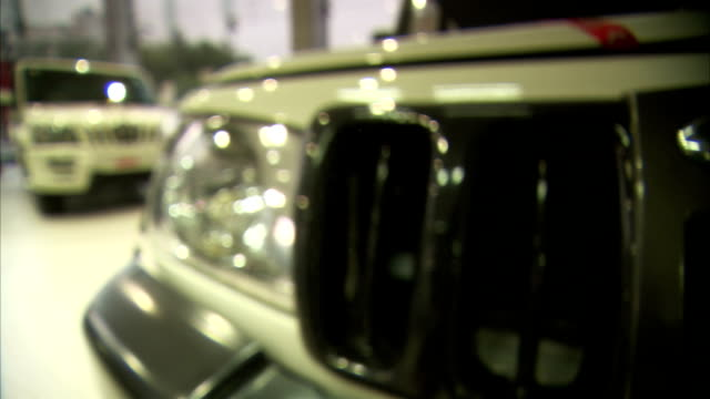 The grille of a vehicle reflects showroom lights at a Mahindra car dealership in Delhi, India.