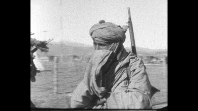 the group of men lead donkeys and camels carrying goods in an arid barren area with mountains in the background some men are wearing rifles and... - bandolier stock videos & royalty-free footage