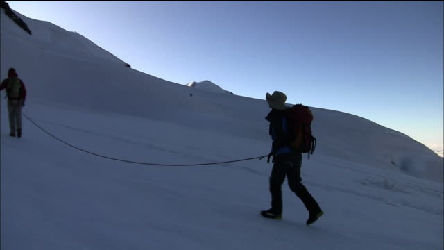 the guide and the climbers walk on the snow field of the klein matterhorn - mountain range stock videos & royalty-free footage