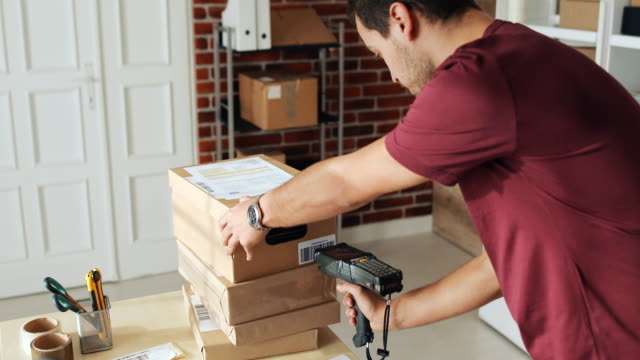 the guy in his office prepares packages that are ready for delivery. - label stock videos & royalty-free footage