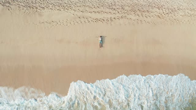 the guy lies on a sandy beach on a tropical island. drone view - sdraiato video stock e b–roll