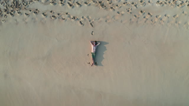 the guy lies on a sandy beach on a tropical island. drone view - sunbathing stock videos & royalty-free footage