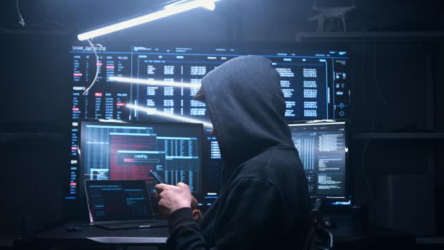 das hacker-mädchen sitzt hinter großen monitoren, sie hackt remote-server. die kamera nähert sich dem hacker von hinten, das mädchen dreht sich scharf um und wir sehen, dass sie den server mit einem mobiltelefon hackt. - spion stock-videos und b-roll-filmmaterial