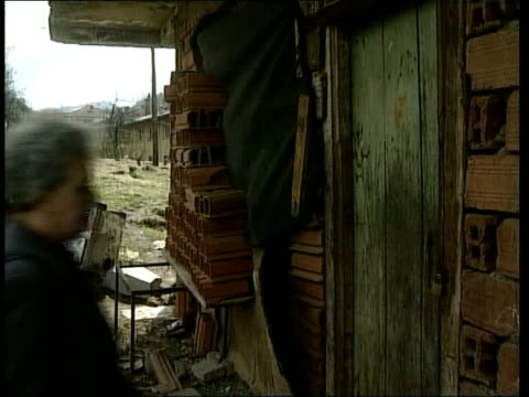 General Radislav Krstic war crimes trial ITN HERZEGOVINA Srebrenica EXT TGV Town TMS Houses one showing bomb damage Advija Sehomerovic along to her...
