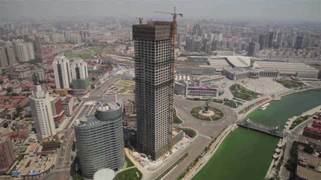 the hai river flows past a skyscraper construction site in tianjin, china. - hai river stock videos & royalty-free footage