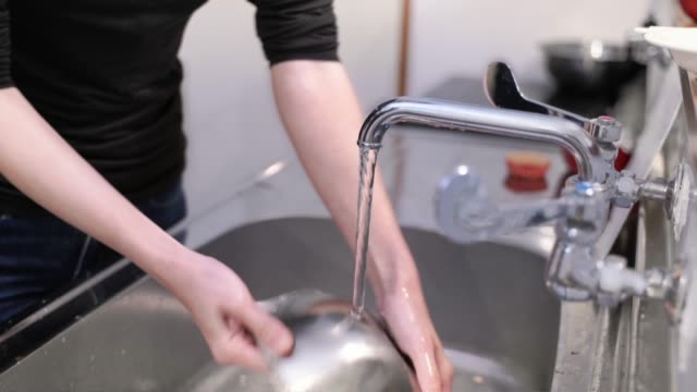 the hand of a woman washing dishes - stereotypical homemaker stock videos & royalty-free footage