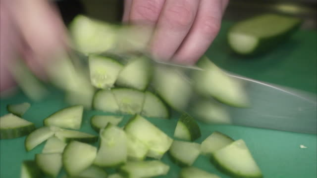 The hands of a cook chopping vegetables in a restaurant kitchen Sweden.