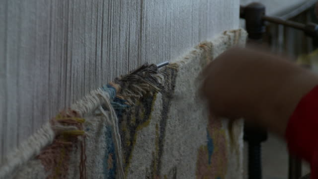 the hands of a tibetan woman tie and cut threads on a loom while weaving at a refugee center. - cut video transition stock videos & royalty-free footage