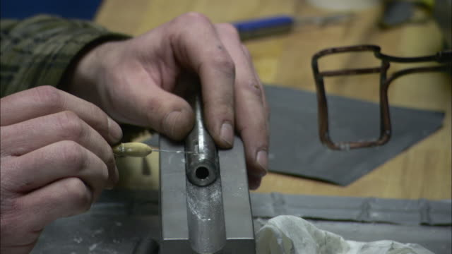 the hands of a worker make adjustments to the barrel of a gun under construction. - gun barrel stock videos & royalty-free footage